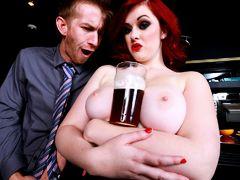 Красная толстая шлюха держит между большими сиськами бокал пива